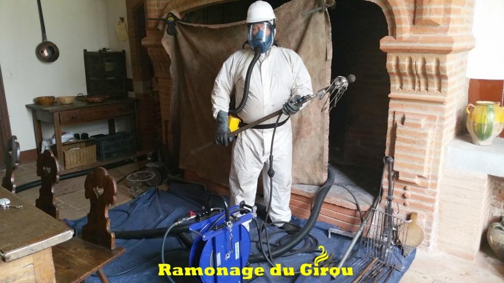 Ramonage d'une cheminée toulousaine. Combinaison et masque ventilé sont nécessaires ainsi que le port du casque.